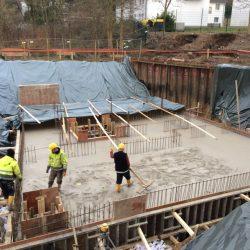 Der Beton ist gegossen und größtenteils bereits geglättet, in einem Areal sind die Bauarbeiter noch mit der Glättung beschäftigt. (Foto: Guido Steinmüller)